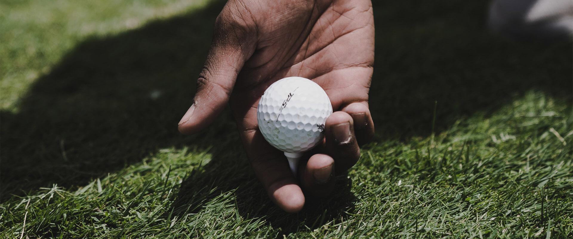 main d'un joueur qui tient une balle de golf